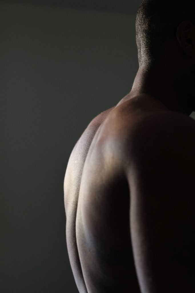 On a dark background, a slightly muscular black back is lit with a bright light. The person has a close-shaved haircut.