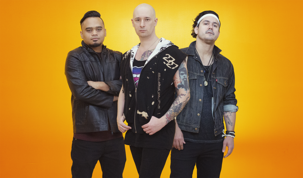 On a bright yellow background, Vattica poses for the camera wearing dark colours, leather and denim. Left to right: Isaac Waters, Alex Millar, Jonny Rosé.