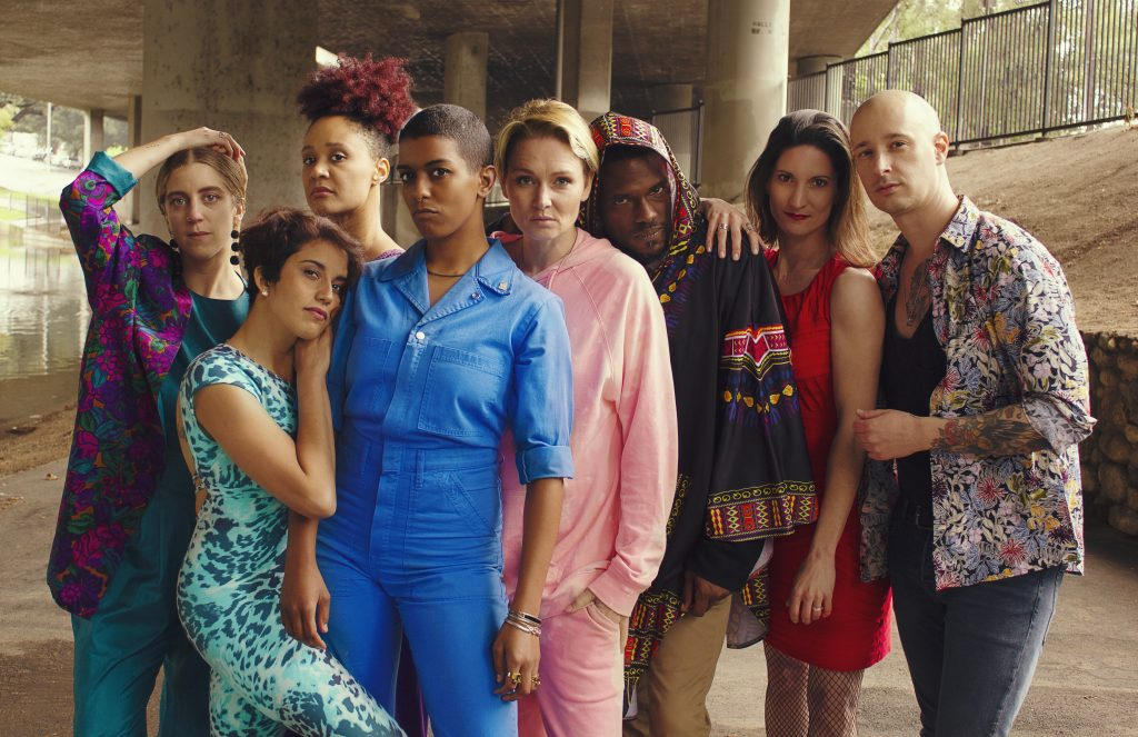 A photo of the Good Trouble Makers, a group of 8 people of different genders and ethnicities, all leaning on each other and looking seriously at the camera. They are all wearing differently coloured bright clothing, and posing under a flyover.