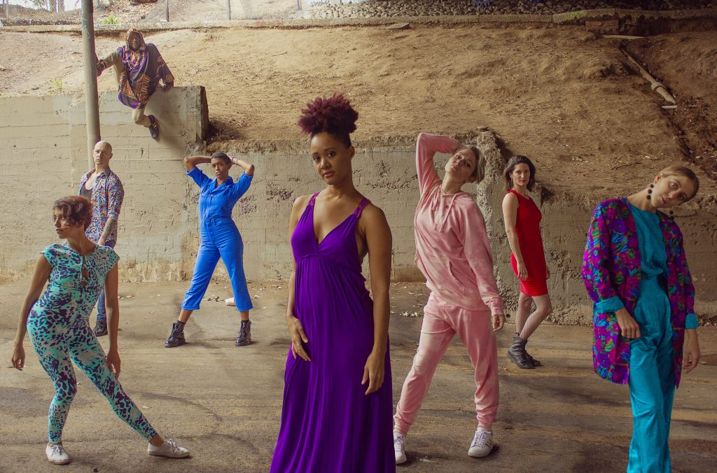 A photo of the Good Trouble Makers, now spread out and posing artistically. Centre front is Kai, an African-American woman with her slightly red hair in a bun on top of her head, wearing a long flowing purple dress.