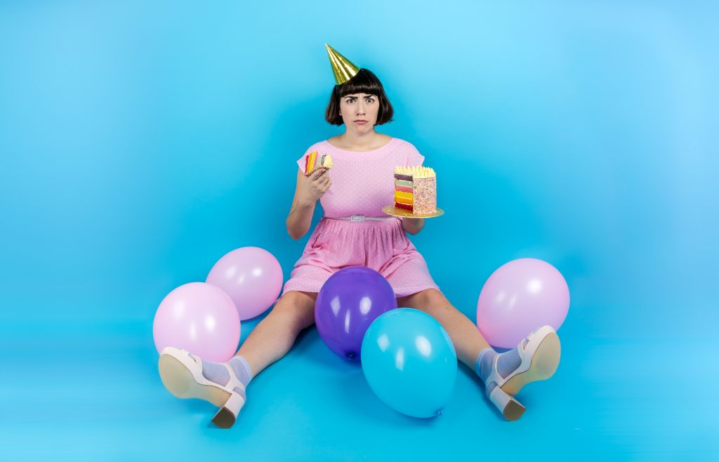 On a bright blue background, Sadie is sitting on her floor with her legs apart, with balloons scattered in and around her legs. She is wearing a gold birthday cone hat, a child-like pink polka-dot dress, and is looking comically concerned. She is holding a plate with a large portion of rainbow birthday cake in one hand, and holding up a half-eaten piece with the other.