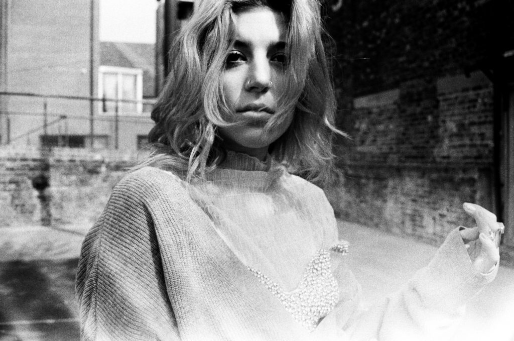 A black and white atmospheric photo of Am.I staring past the camera. Her hair is a loose bob, with her bangs falling slightly across her face. She is wearing a small nose ring on each nostril.
