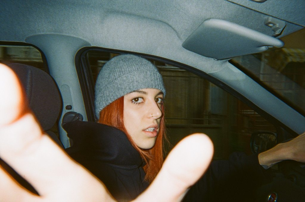 In a car, Am.I reaches to stop a photo being taken, looking caught off-guard. She is wearing a grey beanie and black puffer jacket, with long straight ginger hair.