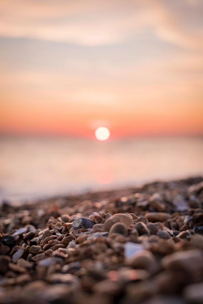 A very blurred, zoomed-in photo of a pebbly beach at sunset. The sun is just a white circle on a warm orange background.