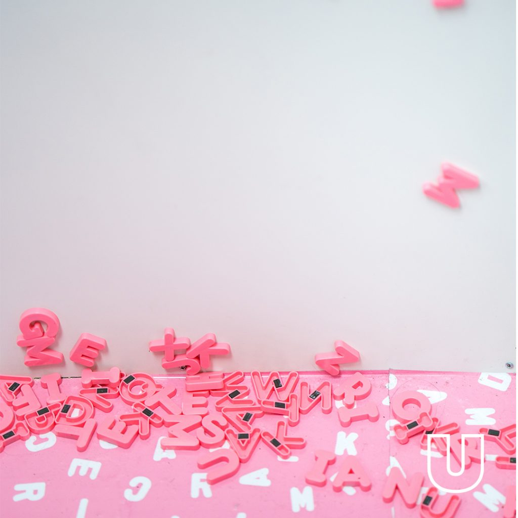 On a sideboard decorated with a pink covering with printed white alphabet letters, a pile of pink alphabet fridge magnets is strewn randomly, a couple of which (Z & M) are stuck to the white panel in the background
