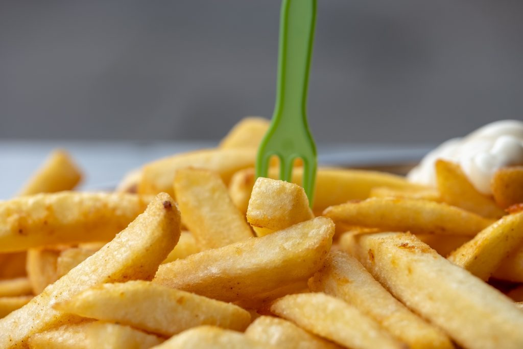 A photo of a large portion of chips, with a dollop of mayo and a green fork sticking out of the pile.