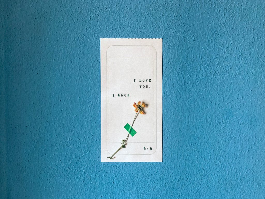 Resting on a blue-painted textured wall, a piece of white receipt paper. On it are the words 'I love you. I know. L.&' typed by a type-writer, the outline of a smartphone drawn in pencil, a small yellow flower, dried and taped to the receipt with green tape.