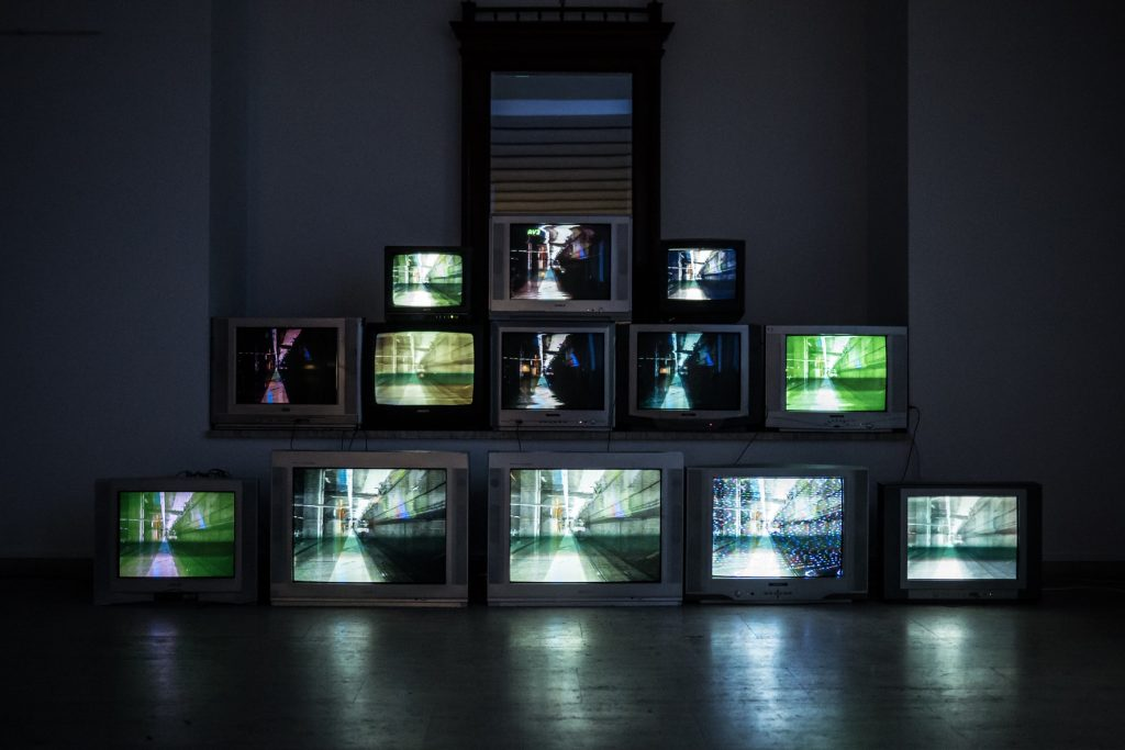 A stack of televisions piled in a pyramid in an otherwise empty room, all showing distorted images of a street in slightly different hues.