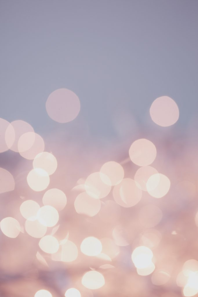 On a pale pink and purple gradient background, light sparkles on the camera, forming pretty dots of lights across the entire picture.