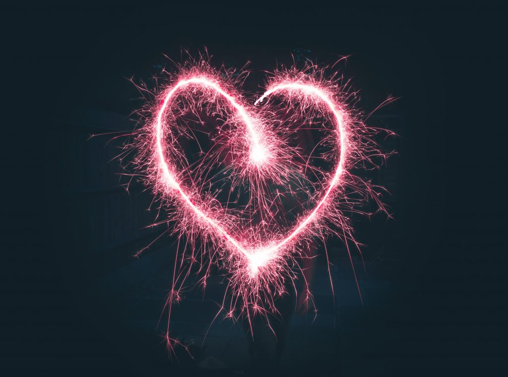 a pink heart is created in the night sky with a firework sparkler.