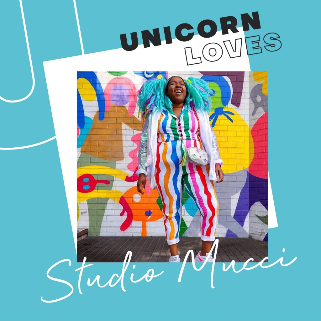 With a blue UNICORN LOVES border, an image of Studio Mucci laughing, with brightly coloured hair and clothing and colourful artwork in the background