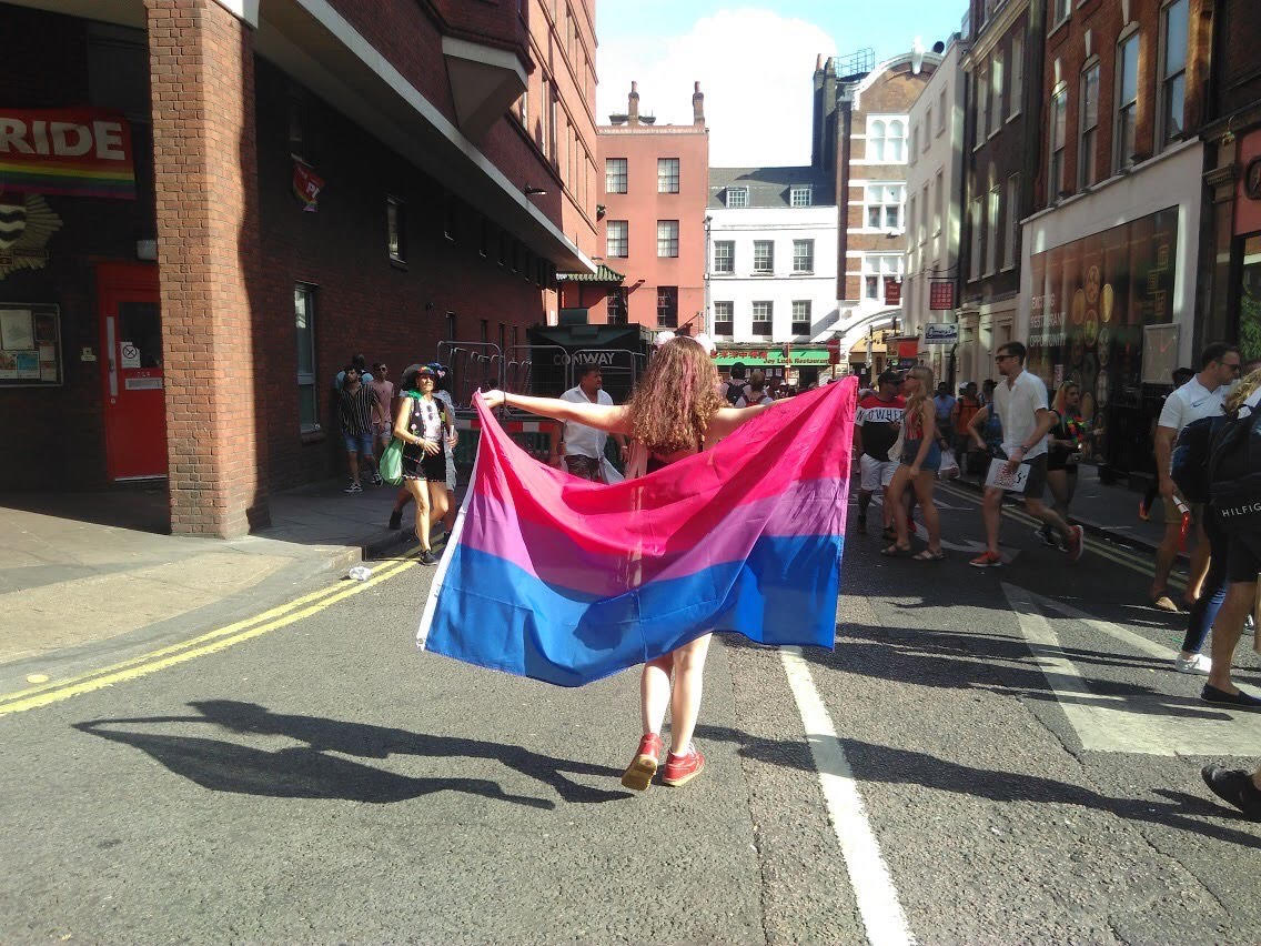 Photograph of the back of Sophia. She is standing with her arms open holding a bi flag which is coloured with pink, purple and blue horizontal stripes. She is standing in the middle of a London street during Pride celebrations. The sun is shining and there are other people crossing the street.