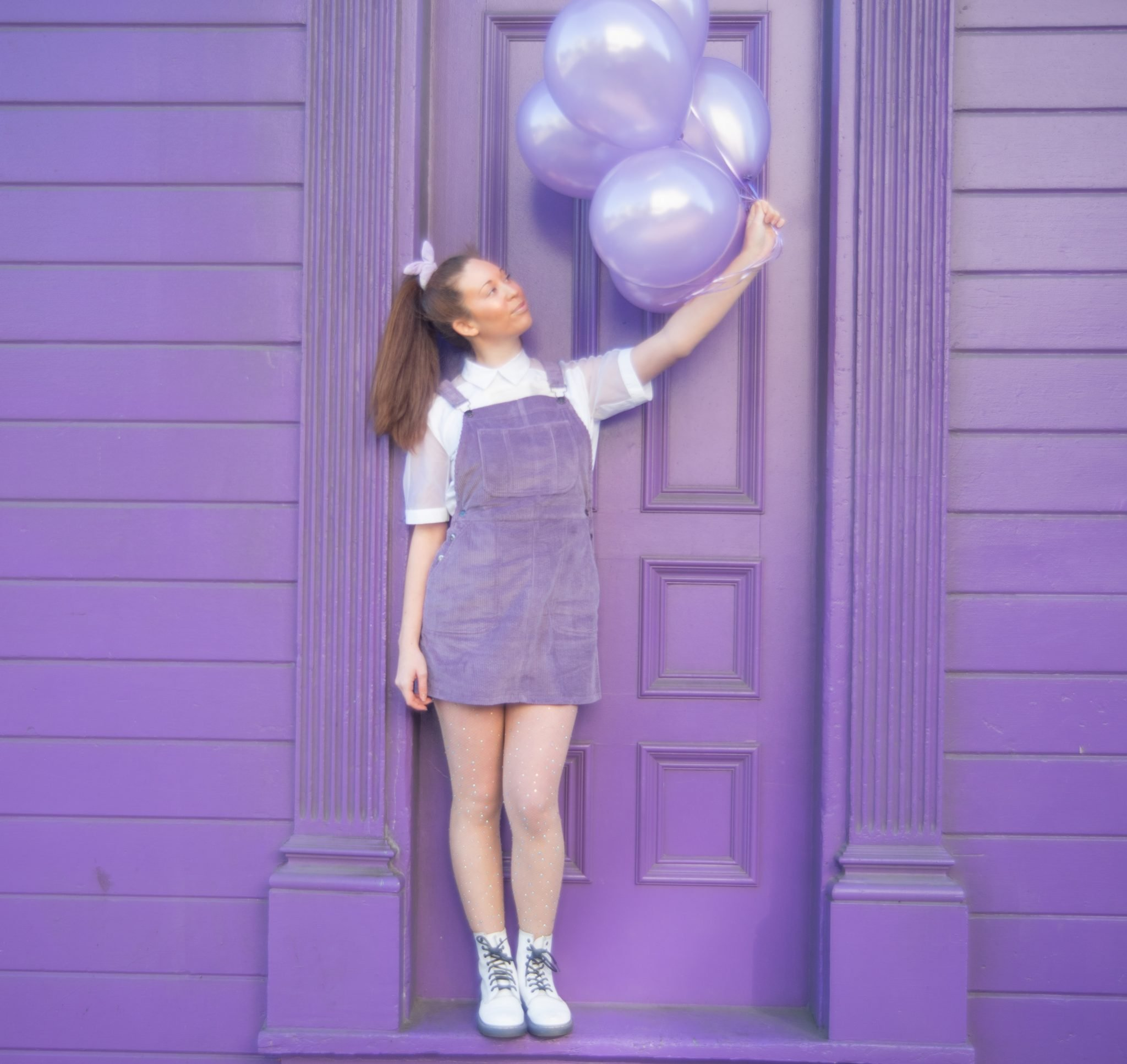 Square photograph of criibaby the singer in front of a lilac wooden house. She is standing on the front step by a wooden door. In her left hand she is holding 6 lilac balloons with ribbon. She is wearing a lilac pinafore dungaree dress with a white shirt. She has long dark hair which is tied up in a ponytail with a lilac scrunchie. She's wearing white boots with black laces.