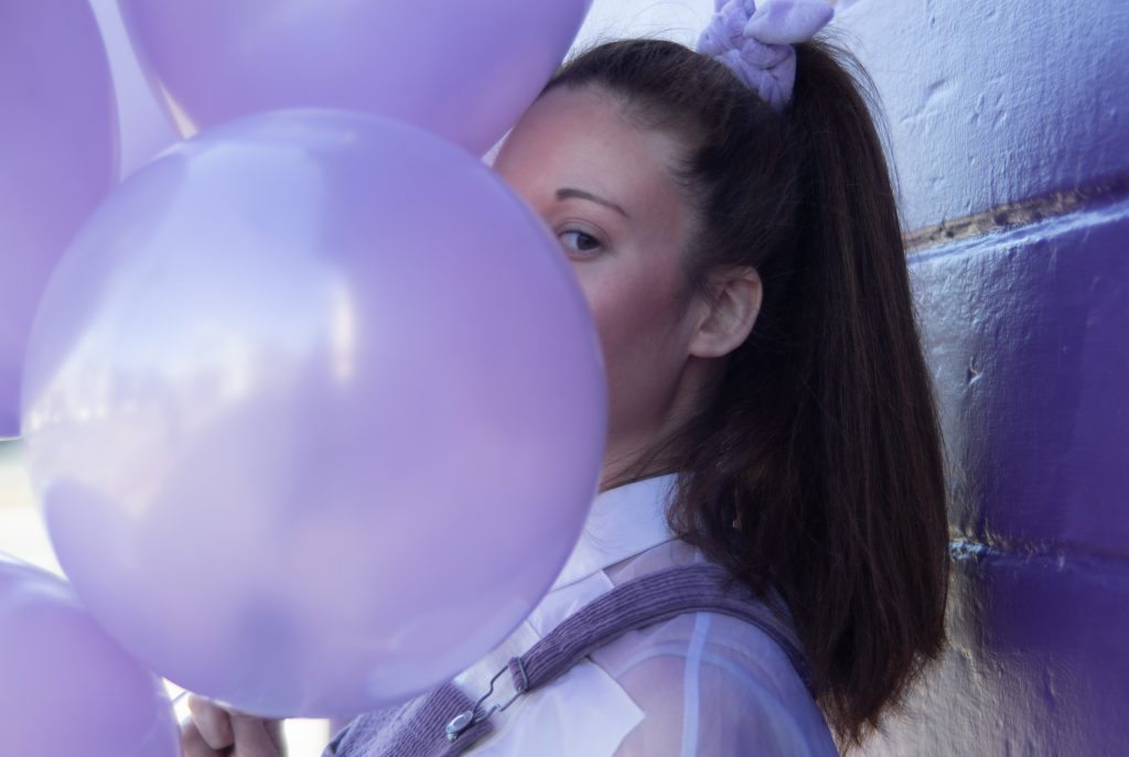 Rectangular photograph. The left handside shows lilac balloons filling the image. Partially hidden behind them is criibaby, the artist. Wearing her dark hair up in a ponytail, tied with a lilac scrunchie. Her hair is long. We see only her left eye peeking behind the balloon. She is standing by a lilac painted wall. She is wearing a white shirt with a lilac pinafore dress over the top.