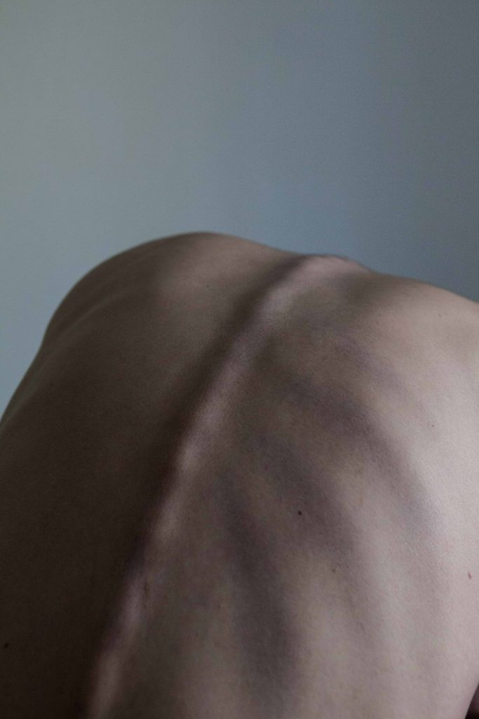 Photography of a naked human back. We see the spine and rib cage in a lot of detail. The image is in colour but saturated, greys and pinks. The back is curved as if the head is hanging down. We only see the back and above it some grey space / background.