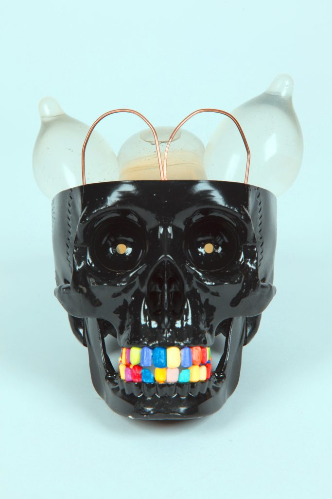 Pastel blue background. Photographed image of a black plastic human skull with an array of coloured teeth. The crown of the skull is cut off to show a copper wire in the shape of the letter M sticking out and 3 plastic, clear condoms filled with air.