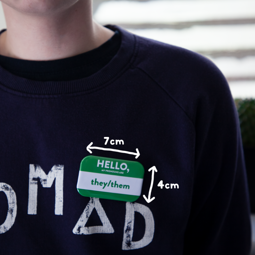 """badge that reads """"they/them"""" with measurements showing that it is 7cm x 4cm in size."""