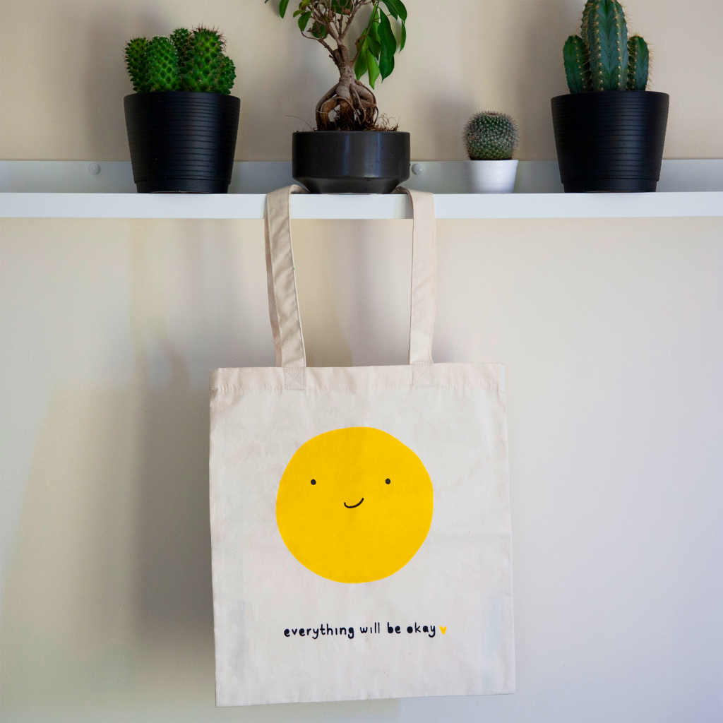 """A tote badge with a smiling yellow face that reads """"everything will be okay."""