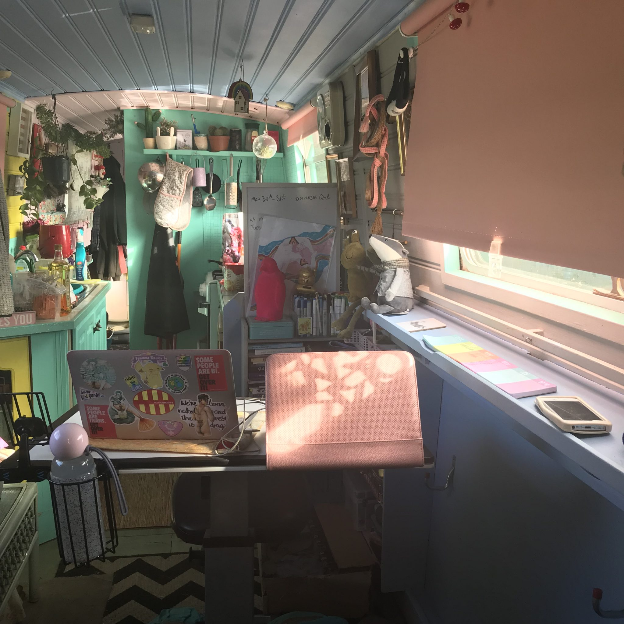 Photograph of the inside of Klara's house boat. We can see a window on the right with a pastel pink blind which is pulled down ¾ of the way. On the windowsill is pastel coloured post-it note pads and a mobile phone. In the middle of the image we see a desk with a laptop which is covered in stickers, a water bottle and other art equipment. Behind this is a green kitchen with utensils and plants.