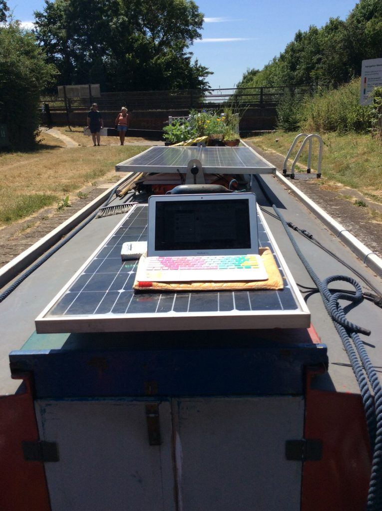 Photography standing on the houseboat deck. We see from the point of view of the deck looking down along the roof of the boat. On top of the roof is a long navy rope which is on the right hand side. In the middle are solar panels and plants. In the foreground, on top of the solar panel is a silver laptop which is open and has a pastel rainbow coloured keyboard. The sun is shining, there is a bridge ahead and two people walking along the grass in the far right corner.