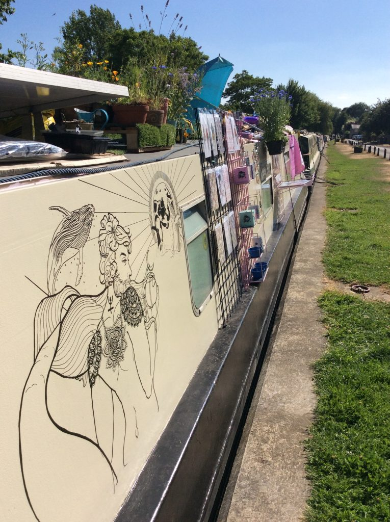 Outdoor photograph where we see part of the side of the house boat. The boat is a pale cream colour with black line illustrations painted on. We also see some of the side of the canal where it meets the land with patches of grass, trees in the background and a bright blue sky.