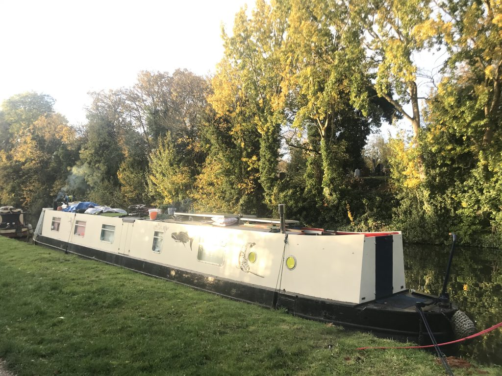 Full shot of the cream illustrated house boat parked along the canal next to some green grass and green, yellow trees.