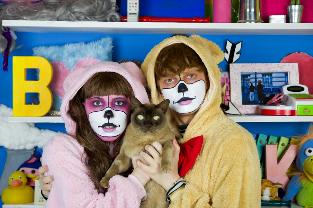 'Bare' (Right) and 'Klare' (Left) are standing in a blur room with white shelved filled with childrens toys. Bare has a neutral face, Klare has a small smile. They are both holding a siamese colour fluffly cat in the middle which is looking to the camera.
