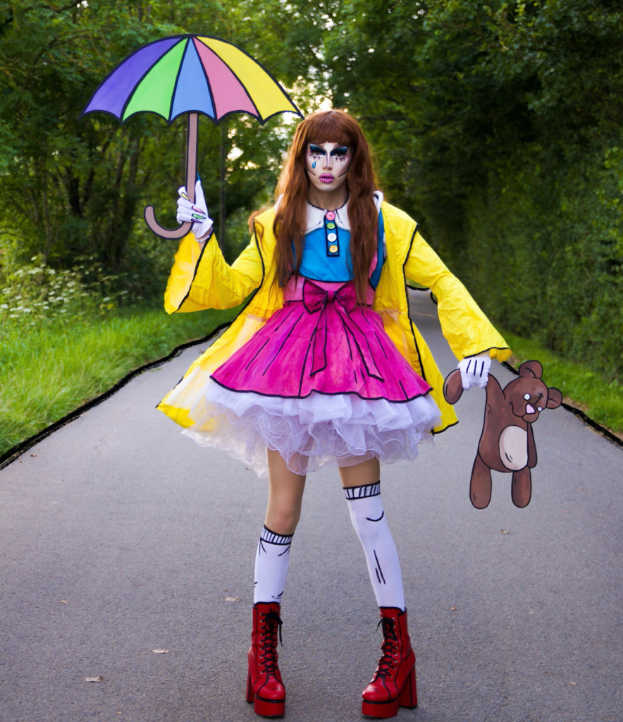 Scaredy Kat (Alex Cubb) is dressed in drag standing in the middle of a rural road, there are trees lining the road each side. They are dressed in a yellow mac, pink skirt and blue top with all the outlines drawn in black marker, to look like a cartoon. They are holding a cutout of a bear drawing and an umbrella. They have pink lips, harsh blue eye makeup and long brown hair.