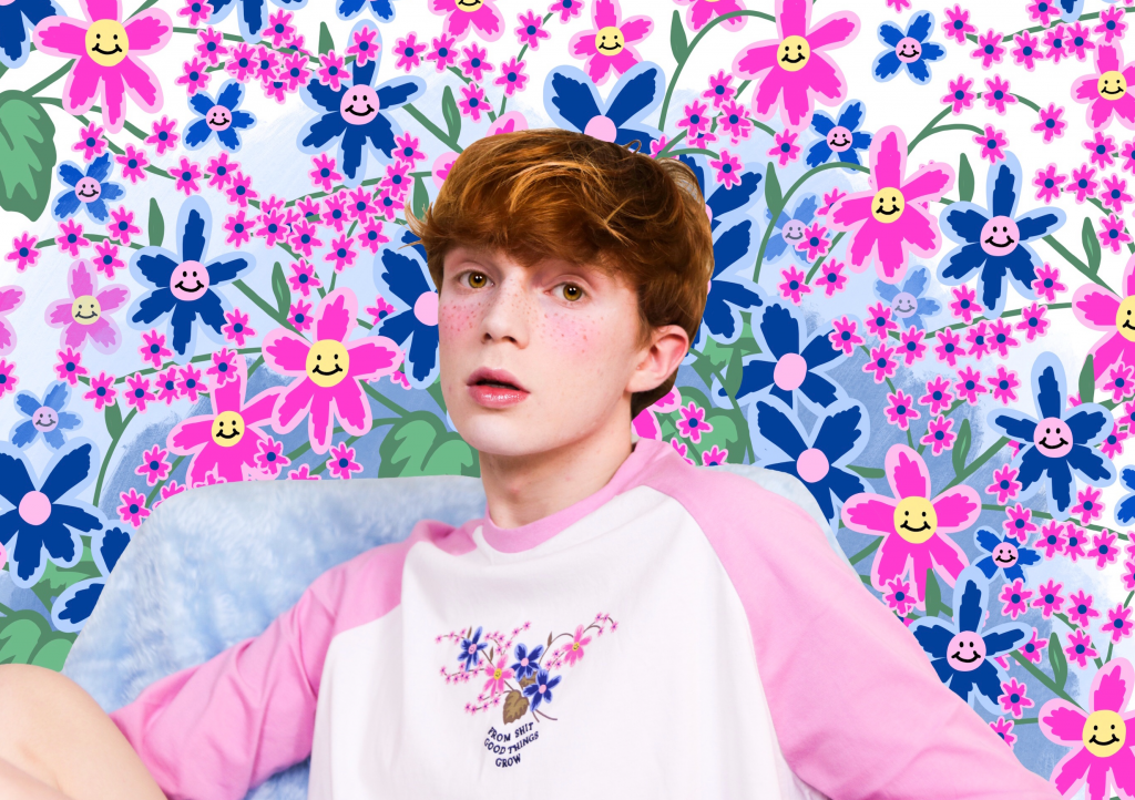 Alex is sitting on a baby blue fluffy chair. the wall behind has been drawn on with smiley pink and blue flowers and green vines. Alex is wearing a raglan style shirt with pink sleeves. The shirt says 'FROM SHIT GOOD THINGS GROW' and shows the same flower design as the walls. Alex has light brown short hair and subtle makeup on with pink cheeks and drawn on freckles.