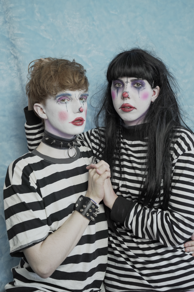 Alex is to the left and is wearing a thick black and white striped t-shirt with faux leather spiked wrist and neck cuffs. He has clown style makeup, white face, red cheeks, lips and nose. He has light brown short hair. Remi is to the right, she is wearing a long sleeved thin striped black and white t-shirt. She has similar makeup to Alex with darker eye makeup. Her hair is long and dark with a short full fringe. They are facing the camera, Remi has her hand in Alex's hair and they are holding hands in the middle of the photo. The background is a light baby blue faux fur blanket.