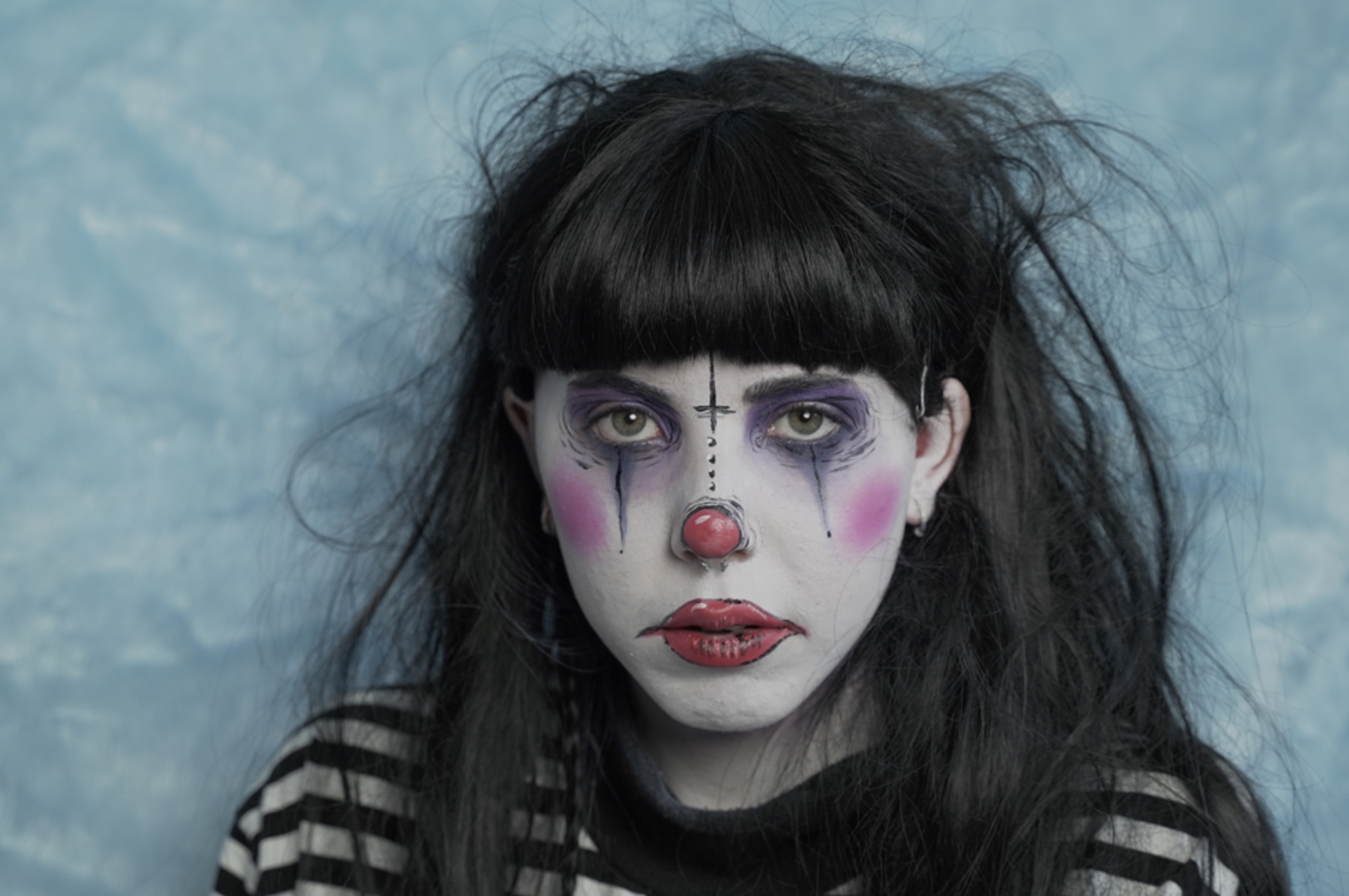 Remi is to the right, she is wearing a long sleeved thin striped black and white t-shirt. She has clown style makeup on with a gothic twist. Red lips, cheeks and nose with dark smudged eye makeup. Her hair is long and dark with a short full fringe. She is facing the camera with a neutral expression. The background is a light baby blue faux fur blanket.