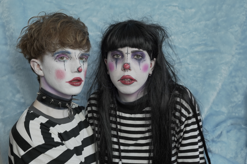 Alex is to the left and is wearing a thick black and white striped t-shirt with faux leather spiked wrist and neck cuffs. He has clown style makeup, white face, red cheeks, lips and nose. He has light brown short hair. Remi is to the right, she is wearing a long sleeved thin striped black and white t-shirt. She has similar makeup to Alex with darker eye makeup. Her hair is long and dark with a short full fringe. They are facing the camera, Only from chest up is visible. The background is a light baby blue faux fur blanket.