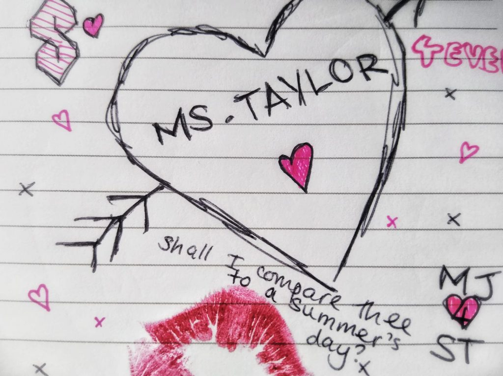 on a lined school notebook, several teenage crushscribbles in black and pink biro, including a giant heart with 'Ms. Taylor 4ever', 'MJ 4 ST', 'Shall I compare thee to a summer's day', a lipstick kiss mark and various hearts and kisses