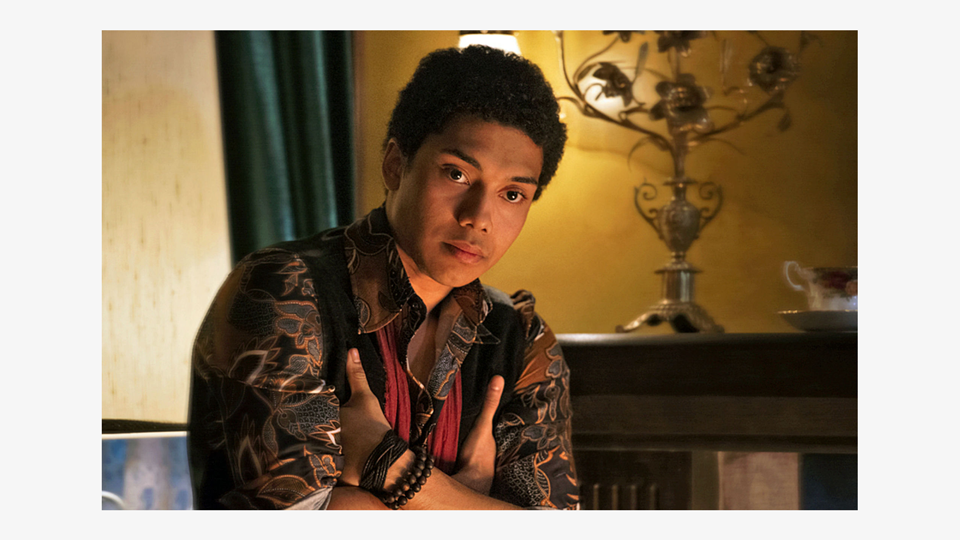 a photo of Ambrose Spellman (Chance Perdomo), a young black man, with his hands tucked up under his arms, staring intently at a character off-screen. He is wearing an ornately patternd black and bronze shirt, a waistcoast, and wooden bracelets. In the background, a living room with a yellow wall, curtains, a candelabra and a teacup.