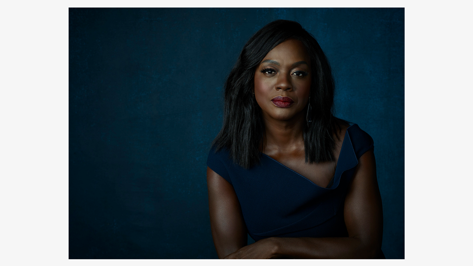a photo of Annalise Keating (Viola Davis), a black woman with shoulder-length hair, wearing a sophisticated navy blue dress against a lighter blue background, leaning on the back of an opulent looking chair and staring intensely into the camera lens