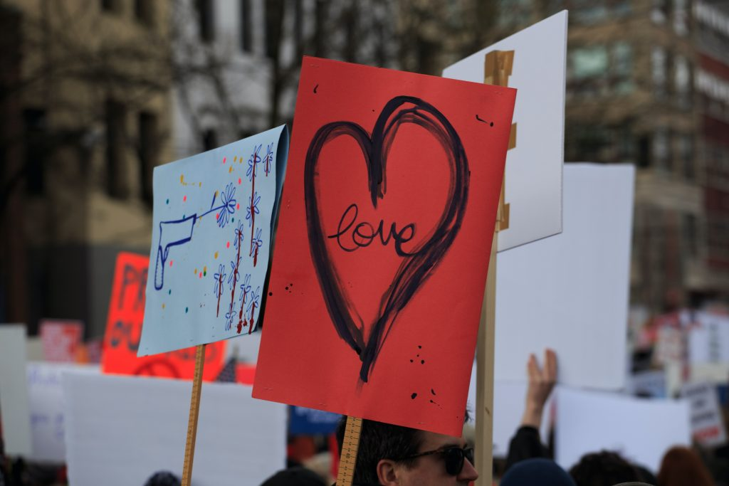 People holding up signs at a protest, the two prominent ones in the photo are a sign that says love inside a love heart, and a doodle of a toy gun shooting flowers