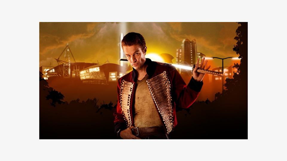 a photo of Captain John Hart (James Marsters), a white male with short hair wearing a military-style red jacket in a casual fashion and pouting sexily at the camera. With one hand, is holding a samurai sword behind his back, and with the other, holding his belt. In the background, a blurred visual of the Millenium centre in Cardiff with an orange, sci-fi hue.