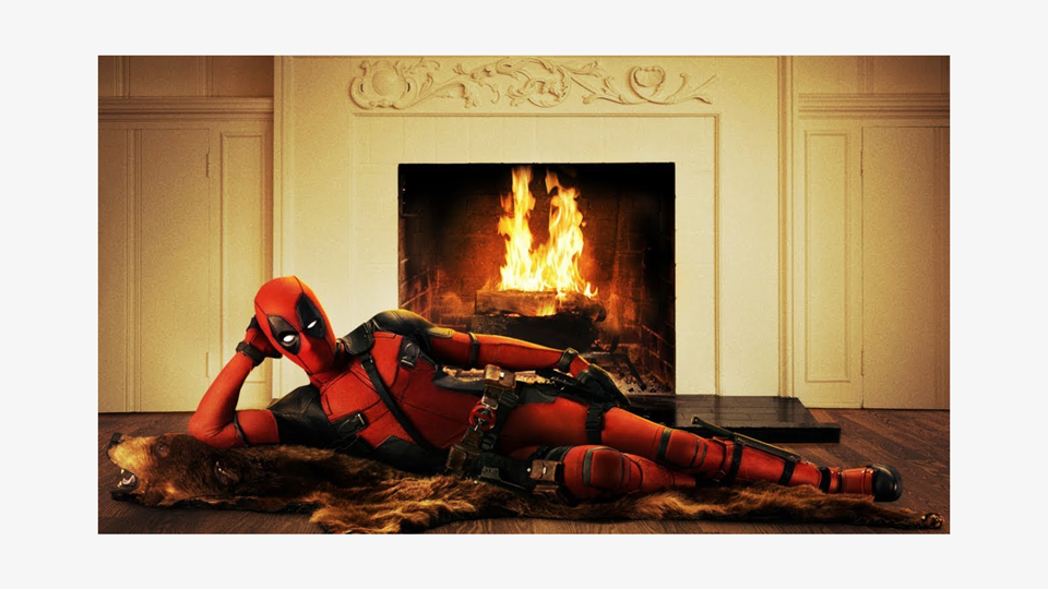 a photo of Deadpool, a superhero in a red and black bodysuit, reclined on a bearskin rug in front of a roaring fireplace. He is posing sexily but comically on his side, leaning on his hand and staring at the camera.