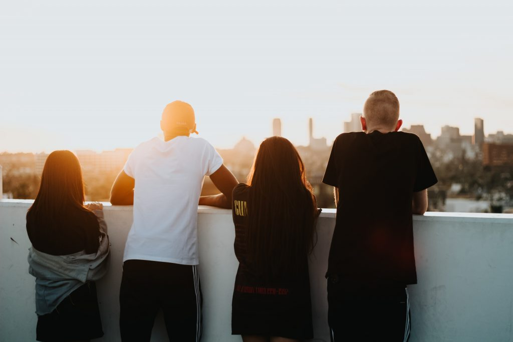 Four people leaning over a balcony looking into a sunset and cityscape