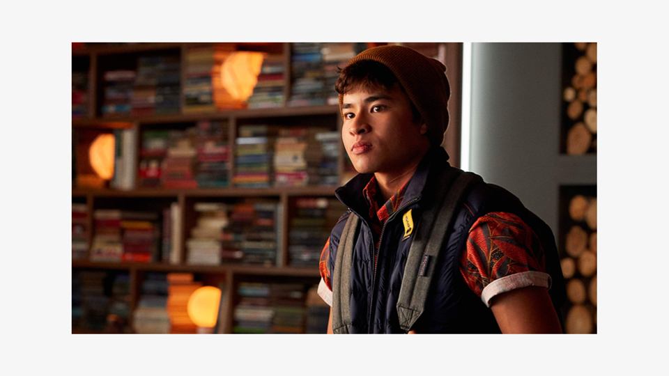 a photo of Jericho (Chella Man), an Asian man, is looking at something off-picture, wearing an orange beanie a body warmer and a backpack. In the blurred background, a library and a pile of logs of a fire.