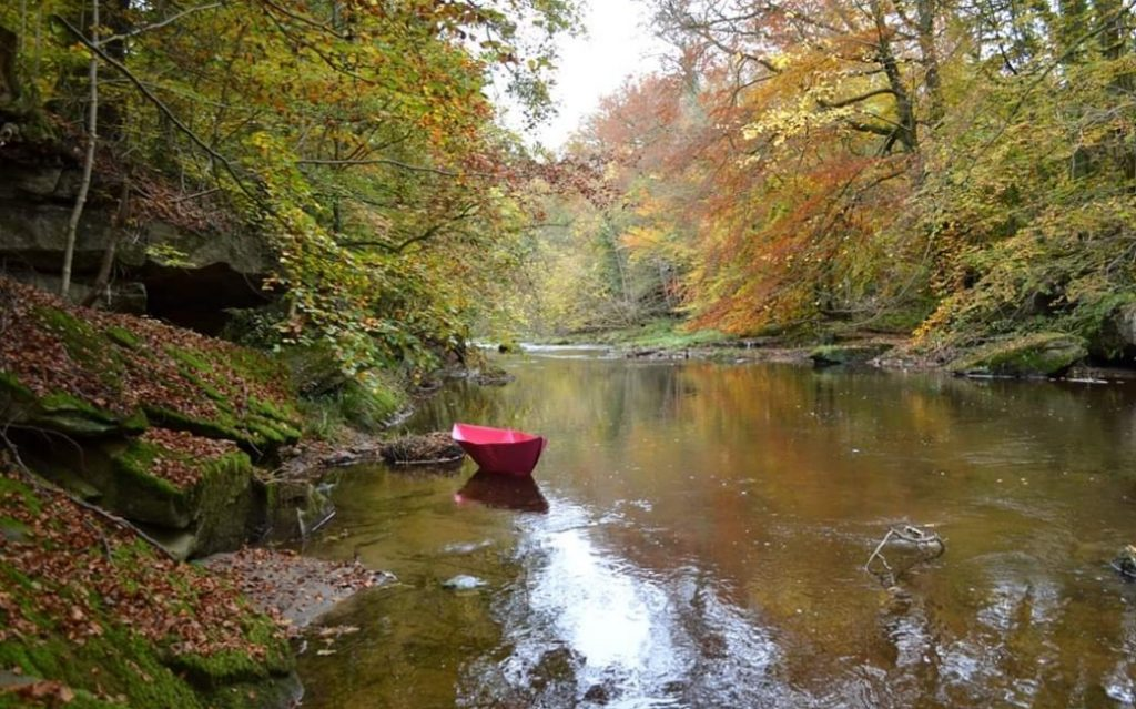 Photograph of a river with autumnal trees either side, in the river floats a huge, pink, origami boat. Image credit: Elaine Robertson