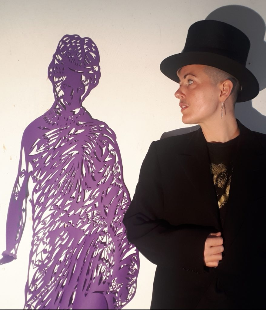 Kitt, a shaven headed human, wearing a top hat and tails stands looking adoringly at a large(the same height as Kitt), intricate paper cut of Sappho, made from purple paper hung against a white wall.