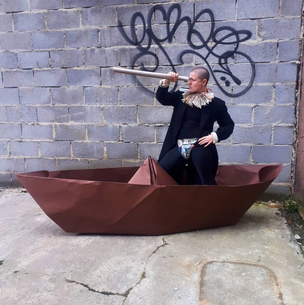 Kitt, a shaven headed human, stands cockily in a giant brown paper origami boat. They are wearing a black top, trousers and coat plus an Elizabethan style ruff and codeice made out of bank notes.