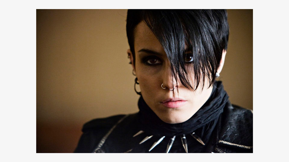 a photo of Lisbeth Salander (Noomi Rapace), a white female, staring intimidatingly to the side of the camera. She has short black hair, heavy dark eyeliner, two small nose rings, and is wearing a black scarf and a scarily-spiked metal choker