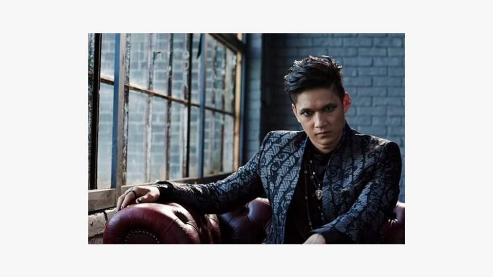 a photo of Magnus Bane (Harry Shum Jr.), an Asian male wearing a flamboyant black blazer, brushed metal necklaces and gothy eyeliner, is staring intensely at the camera in an exposed brick room with a large framed window
