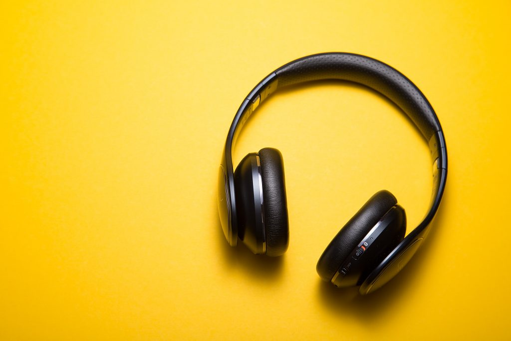 On a bright yellow background, a pair of black wireless headphones