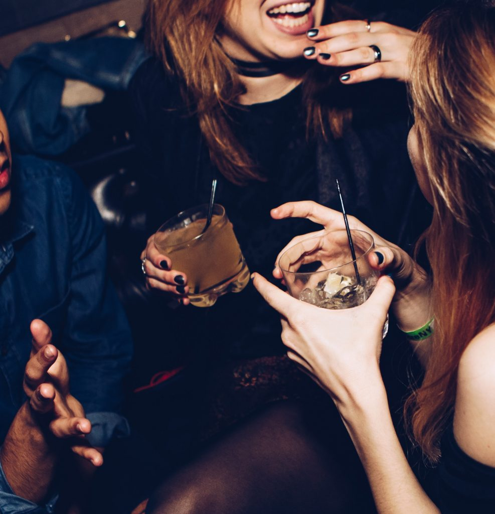 a shot of two friends holding drinks at a nightclub, sitting and chatting with another person just slightly in photo frame.