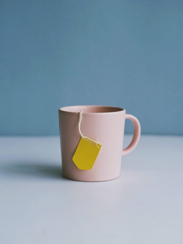 A very pale pink cup, with a blank yellow tea-bag label sticking out, is resting on a surface with a blue background