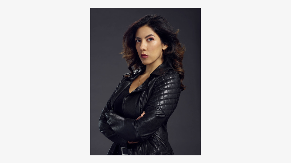 a photo of Latina detective Rosa Diaz (Stephanie Beatriz), arms crossed, staring with determination at the camera with her long hair flicked back. She is wearing a leather jacket.