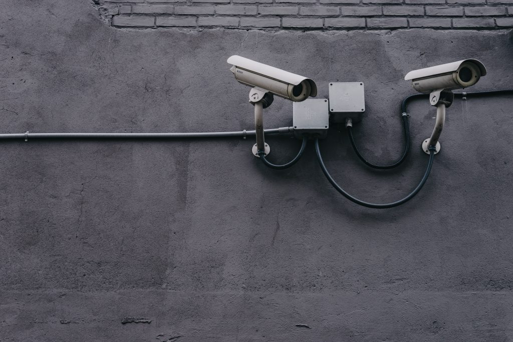 a shot of two security cameras looking onwards, mounted on a grey wall.